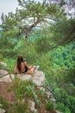La muchacha con el teléfono se sienta en una roca rodeada por los pinos verdes imágenes de archivo libres de regalías