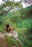 La muchacha con el teléfono se sienta en una roca rodeada por los pinos verdes fotografía de archivo libre de regalías