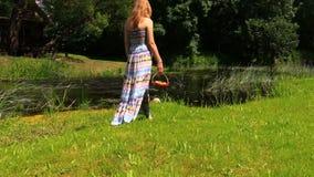 La muchacha con el vestido largo va a lo largo de la cesta disponible del río de fruta Fotos de archivo