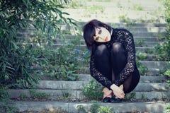 La muchacha con estilo se sienta en la escalera. Fotos de archivo libres de regalías