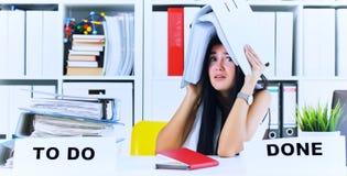 La muchacha con exceso de trabajo divertida con una carpeta en su cabeza que se sentaba en el lugar de trabajo estorbó con las ca Fotos de archivo