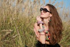 La muchacha con joyería y vidrios se sienta en campo de hierba imagen de archivo libre de regalías