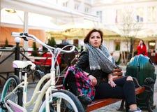 La muchacha con la bicicleta del vintage se sienta cuidadosamente en vieja plaza Imagen de archivo libre de regalías