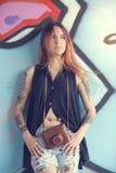 La muchacha con la cámara del vintage contra la pared de la pintada mira lejos Imagenes de archivo