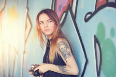 La muchacha con la cámara del vintage contra la pared de la pintada mira lejos Fotos de archivo