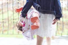 La muchacha con la capa del dril de algodón y la primavera visten el escalonamiento hacia fuera con la muñeca Imagen de archivo libre de regalías
