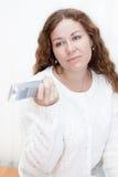 La muchacha con la cara amarga cambia los canales con el telecontrol de la TV Imágenes de archivo libres de regalías