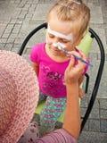 La muchacha con la cara pintó Foto de archivo libre de regalías