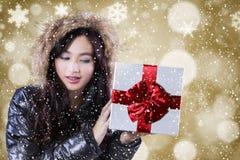 La muchacha con la chaqueta del invierno sostiene la caja de regalo Fotos de archivo