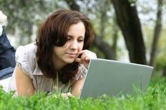 La muchacha con la computadora portátil en la naturaleza Fotos de archivo libres de regalías