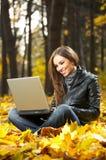 La muchacha con la computadora portátil Fotos de archivo