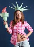 La muchacha con la corona y la antorcha representa la estatua de la libertad. Fotos de archivo libres de regalías