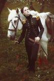 La muchacha con la espada del cuento se coloca al lado de un caballo blanco Foto de archivo