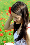 La muchacha con la flor de la amapola Imagen de archivo