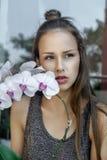 La muchacha con la flor de la orquídea está muy triste Imagenes de archivo