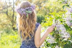 La muchacha con la guirnalda de la lila florece en parque verde Fotografía de archivo