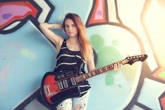 La muchacha con la guitarra eléctrica se coloca cerca de la pared de la pintada Fotos de archivo libres de regalías