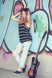 La muchacha con la guitarra eléctrica se coloca cerca de la pared de la pintada Foto de archivo libre de regalías