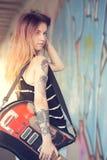 La muchacha con la guitarra eléctrica se coloca cerca de la pared de la pintada Fotografía de archivo