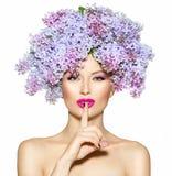 La muchacha con la lila florece el peinado imagen de archivo