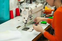 Muchacha con una máquina de coser Fotografía de archivo libre de regalías