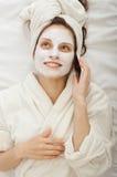 La muchacha con la máscara poner crema habla por el teléfono Imagen de archivo libre de regalías
