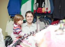 La muchacha con la madre alegre elige desgaste Imagen de archivo