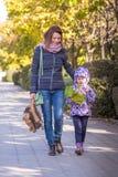 la muchacha con la madre de las hojas de otoño va a la pista en el parque Fotografía de archivo libre de regalías