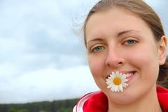 La muchacha con la manzanilla en dientes Fotos de archivo