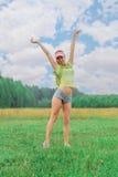 La muchacha con la mochila que se colocaba al aire libre con los brazos aumentó hasta Imagen de archivo libre de regalías