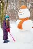 La muchacha con la pala se coloca al lado del muñeco de nieve grande Fotos de archivo