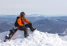 Muchacha con la snowboard encima de la montaña Imagen de archivo