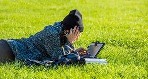 La muchacha con la tableta, mintiendo en hierba verde y escribiendo en la tableta agujerea de la preparación Fotos de archivo