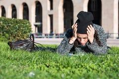 La muchacha con la tableta, mintiendo en hierba verde y lleva a cabo su cabeza con las manos Fotos de archivo libres de regalías