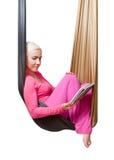 La muchacha con la tableta que descansa en la hamaca de la ejecución Fotografía de archivo