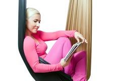 La muchacha con la tableta que descansa en la hamaca suspendida para la yoga Fotografía de archivo libre de regalías