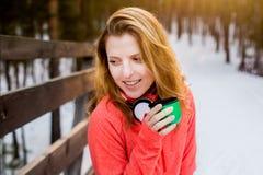 La muchacha con la taza en parque del invierno Imagenes de archivo