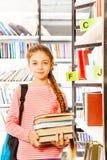 La muchacha con la trenza sostiene los libros cerca del estante Imágenes de archivo libres de regalías