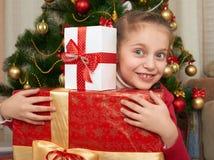 La muchacha con las cajas de regalo acerca al árbol de navidad, celebración feliz del día de fiesta y del invierno Fotografía de archivo libre de regalías
