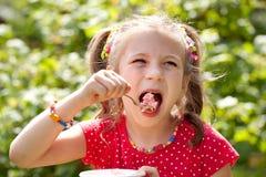 La muchacha con las coletas come con helado del condimento Foto de archivo libre de regalías