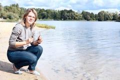 La muchacha con las gafas de sol acerca al agua Imagen de archivo libre de regalías