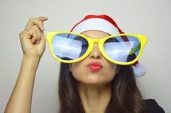 La muchacha con las gafas de sol y el sombrero divertidos grandes de Santa Claus celebra la Navidad Imagen de archivo