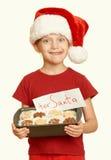 La muchacha con las galletas para santa, concepto de la Navidad de las vacaciones de invierno, amarillea entonado Imagen de archivo libre de regalías