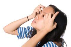 La muchacha con las manos en el pelo mira hacia arriba Fotos de archivo