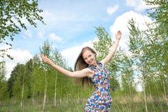 La muchacha con las manos levantadas contra el cielo Fotos de archivo libres de regalías