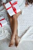 La muchacha con las piernas hermosas sostiene la caja blanca envuelta con la cinta roja fotos de archivo libres de regalías