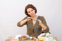 La muchacha con las tijeras corta la cinta decorativa alrededor de la tabla con costura Foto de archivo libre de regalías