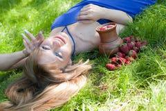 La muchacha con leche y una fresa Fotos de archivo libres de regalías