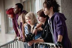 La muchacha con los amigos mira la cámara Imagenes de archivo