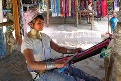 La muchacha con los anillos de cobre teje un paño Imagen de archivo